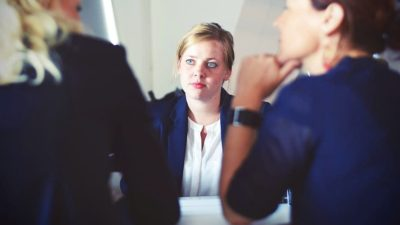 How can businesses attract more women into leadership positions?
